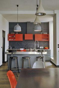 steingraue Wandfarbe, orange Oberschränke, Edelstahl Arbeitsplatten