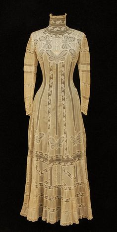 Edwardian fashion, women's 1900s dress, HIGH NECK TEA GOWN with LACE BUTTERFLIES, EARLY 20th C. 1-piece princess style cream cotton batiste inset with vertical bands of lace and net, embroidered yoke inset with lace butterflies, boned neck, banded sleeve with fine tucks, skirt having band of butterflies below hip over pieced lace and embroidery, gathered hem bands. Bust 30, waist 22, length 54.