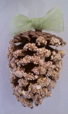FOR THE BIRDS :: DIY Pine Cone Bird Feeder :: Gather some pine cones, peanut buter, bird seed & ribbon to make this easy feeder | #birds #birdfeeder #pinecones
