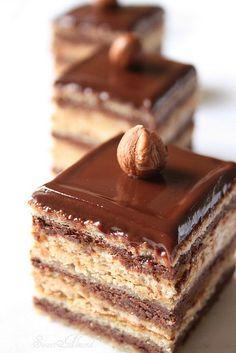 Torta ópera: strati di pasta biscotto alle noci, biscotto al cioccolato, sciroppo al caffè, crema al burro al caffè e grana che al cioccolato fondente.
