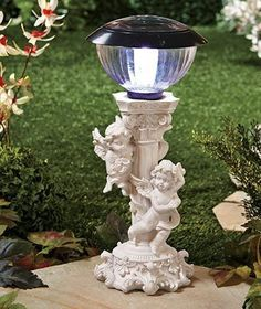 "Solar Cherub Light . $23.50. The intricate details of the Solar Cherub Light make it the perfect addition to any garden! The two little angels dance around the decorative pedestal while the white light glows on top. It collects energy from the sun to power its light throughout the nighttime hours. Includes an on/off switch. 14-1/4"" x 6-1/4"" dia. Cold cast ceramic.      Sculpted details make this standout decor     Details:         Includes on/off switch         14-1/4"" x..."