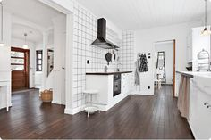 biała kwadratowa płytka z czarnymi spoinami na ścianie kuchennej z czarnym okapem, brązowa ciemna podłoga z desek na podłodze w białej kuchni - Lovingit.pl