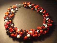 handmade necklace made of red coral chips, black glass chips, red round chaolitis beads and black-white beads