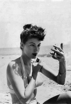 1940... Putting lipstick on at the beach, Love it!