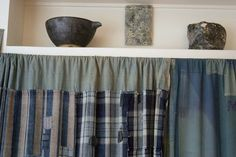 The closet is concealed behind drapes made from Japanese mosquito netting and the patched and mended indigo fabrics known as boro.    On the shelf above: a ceramic bowl by Akio Nukaga, a bronze plaque by Los Angeles sculptor Ricky Swallow and one of Breslin's handmade ceramic pieces.