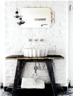 Austere black against white, but is softened by the painted bricks, the round sink, the comfy looking towels.  Slightly asymmetrical, just slightly with the hanging pendant lights.  It's a great composition.  #organic_green_and_beautiful_re-use