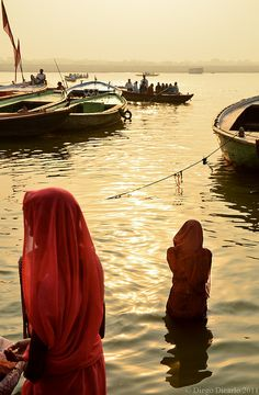 INDIA: women in red sarees in the Ganges River, Varanasi