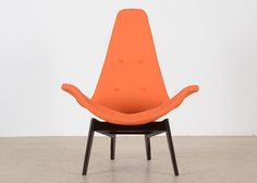 A stunning Mid Century Danish Modern sculptural wing chair, in the style of Adrian Pearsall in a vibrant orange tweed upholstery and dressed with dark stained wood legs. Comfortable and stylish, th...