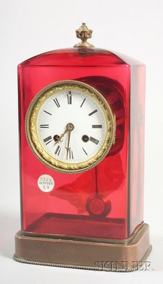 French Cranberry Glass Mantel Clock, early 20th century, retailed by Tiffany and Co., with bronze foliate finial and sloped top above a rectangular case fitted with a half-striking two train Japy Freres movement, with plinth base, ht. 11 3/4 in.