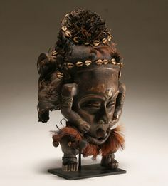 """African Kuba mask, Democratic Republic of Congo. Woven fiber headdress sewn with cowry shells and topped with feathers, applied brass to nose ridge, upper arms, and wrists, also note the interesting facial positioning. On custom stand. 17 1/2""""H."""