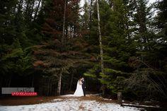 Samantha and Corey get in a kiss in the trees before the ceremony. #wedding #idaho #priestlake #elkinsresort #idahowedding #bride #groom #portrait #kissing #trees #snow