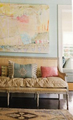 Love the soft wall paint with the modern painting, linen settee & pastel pillows
