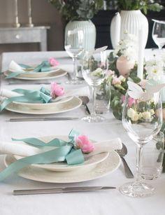 """Hei, alle gode! I dag deler jeg bilder fra det siste av fire konfirmasjonsbord jeg har dekket og fotografert for Tilbords. Dette har vært en morsom jobb i holde på med. Dette bordet er stylet i tema """"Pastell"""", og fremstår lett og feminint. Ønskes bordet mer maskulint, er det bare å skifte ut de rosa ranunklene og hvite rosene til f.eks blåveis, perleblomster og hvite margeritter. Velg også gjerne en annen farge på båndene (eventuelt droppe dem). Som jeg alltid pleier å si; spør konfirmanten…"""