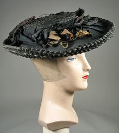 Circa 1900 summer hat has a wide flat brim with a shallow crown. The brim has a circlet of black cotton, a straw cord in loops, and flowers in back and with tan leaves. The underside of the brim shows the straw. The crown is lined in  black cotton.  Via Past Perfect Vintage.