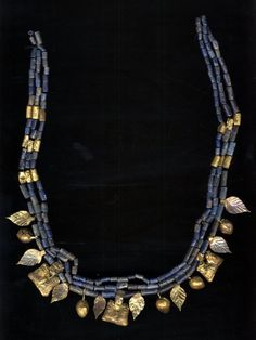 Necklace of gold and lapis lazuli; three strings of beads; 16 gold pendants, 8 leaf-shaped pendants, 5 bud-shaped pendants overlaid with gold, 3 pendants overlaid with gold with two human-headed bulls each, back to back; 15 cylindrical beads overlaid with gold, 172 cylindrical lapis lazuli beads, carved, perforated and polished. Culture/periodEarly Dynastic III term details Date2600BC-2350BC - Asia,Iraq,South Iraq,Royal Cemetery (Ur)