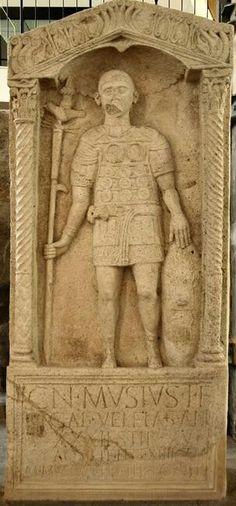 Estela de Cn(eus) Musius, aquilifer de la Legio XIIII Gemina. Mogontiacum / Mainz (antequem 43 d.C.). Altura: 1.96m (2.13m con la reintegración; Anchura: 0.95m; Grosor: 0.32m. (Éspérandieu 5790. CIL CIL XIII 6898 = ILS 2341). Se trata de un hispano, natural de Veleia / Iruña. Landesmuseum Mainz.