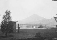 Gezicht op de vulkaan Sumbing vanuit het residentiehuis in Magelang met schildwacht en Boeddhabeeld in de tuin. 03-04-1935.