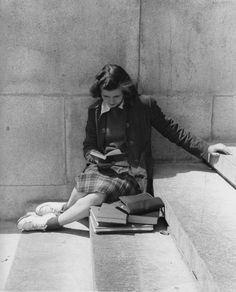 Student, dressed for class, reading on steps, 1950s.