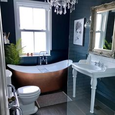 This vintage-inspired bathroom is so elegant. The dark walls and copper bath are a match made in heaven.  . #wholesaledomestic #darkinteriors #vintagebathrooms #victorianbathroom #smallbathroom #bathroomrenovations #bathroominspiration #dreambathrooms #bathroomdecor #bathroomdecor2019 #bathroomdesign #bathroominterior
