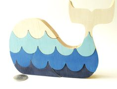 Puzzle whale. Childrens game, wood toy, wooden puzzle, whale puzzle with waves.