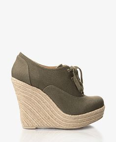 Espadrille canvas wedges featuring a lace-up top. Round toe. Padded insole. Textured outsole.