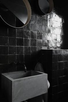 mirrored black tiles against a matte gray tub - dramatic bath space
