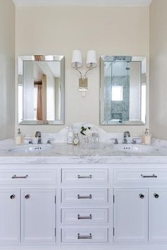 Chic master bathroom boasts a white dual vanity paired with a grey and white marble countertop and a curved marble backsplash under his and hers beveled mirrors illuminated by a 2 light sconce.