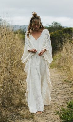 "Part of our 'Ritual Woman' Collection The ""Tatum"" is a bohemian kaftan with chiffon crochet embroidery along the sleeves. Perfect for an untraditional wedding, elopment or rehearsal dinner. The matte satin liner follows the body, leaving the sleeves sheer for a whimsical aesthetic. Features a v neckline and a chiffon tie around the waist. …"