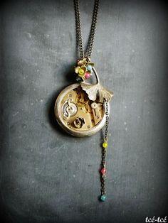Sautoir composé d'une montre gousset ancienne au mécanisme apparent, de pierres de jade et de pièces de laiton.Longueur: 80 cm env.•Pièce unique•