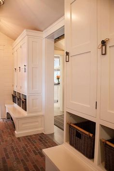 Cottage mudroom w/red brick floor & floor-to-ceiling lockers