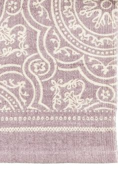 Tapis en coton tissé avec motif imprimé sur le dessus.