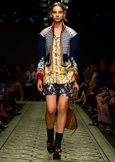 The Cavalry Jacket, adorned with braided regalia and domed buttons, is worn with a wallpaper print shirt and castle print pyjama-style shorts.