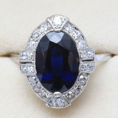 Pretty antique cluster ring, with a large oval faceted sapphire and gorgeous Art Deco surround, pavé set with transition cut diamonds. Made in France circa 1920