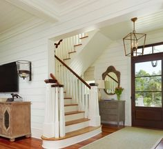 Design Ideas: Small Foyer With A Wire Pendant Light. simple wire pendant light. hard wood flooring. classic mirror frame. wooden stair way. gray wooden chest.