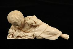 "JAPANESE IVORY - 19th c. Late Meiji Period Okimono of a Reclining Child, resting on her elbow, looking down at her doll, a rattle in her upraised hand. Signed. 4 3/4"" long."