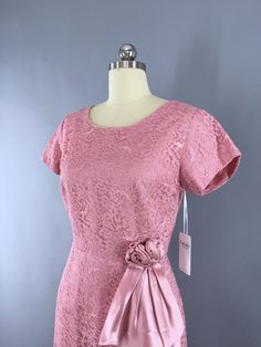 Beautiful vintage late 1950s to early 1960s cocktail dress. Pink lace with a satin rose and sash at the hip, a back metal zipper and lined in matching pink taffeta. In excellent condition. No tags. Dr