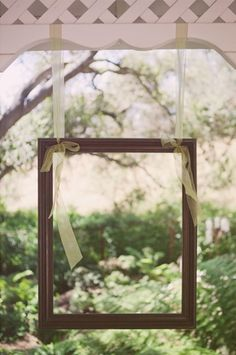 """Hang """"Floating"""" picture frames to create a photobooth for guests. Can also be hung with clear fishing line and Command(TM) Hooks!"""