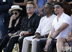 Bono of U2, The Edge and Amnesty International Secretary General Salil Shetty sit with Yoko Ono who holds a tissue to her face as they listen to a musical performance before they unveil a giant 24' x 10' tapestry honoring John Lennon in the presence Amnesty International Secretary General Salil Shetty at the Ellis Island National Museum of Immigration in New York City on July 29, 2015. Photo by John Angelillo/UPI