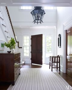 A striped carpet ties together the entrance hall's white walls and dark-wood elements | archdigest.com