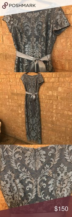 """Major price ⬇️Beautiful column gown worn once! Beautiful dress. Worn once to a black tie wedding. Found one indention on the ribbon which could possibly be fixed by ironing the ribbon. If not, could easily be hidden by tying the bow where the indention is.  I am 5'2"""" and searched high and low for a beautiful gown that didn't drag the floor. With heels, this dress worked for me. The dress is dusty blue with a bronze lace overlay. I wore bronze shoes. This dress has been freshly dry cleaned…"""
