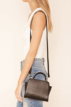 A faux leather trapeze satchel featuring dual top handles, an adjustable shoulder strap, two snap-button compartments, and one interior pocket.