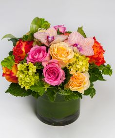 Sea Breeze - A low and lush design of orange, pink and peach roses accented with orchid blooms and simple greens in our leaf-lined cylinder vase.