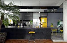 """""""Amarelo me faz bem."""" É com essa frase que o arquiteto Diogo Oliva olha para sua geladeira e justifica a escolha do tom. A cozinha teria tudo para ser sisuda: marcenaria e pastilhas pretas, cimento queimado. Mas ali está a cor"""