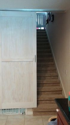 Barn door with pocket track mounted to ceiling at bottom of stairs.