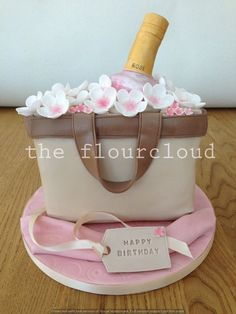A birthday cake with a bottle of rose in a pretty handbag with flowers on.