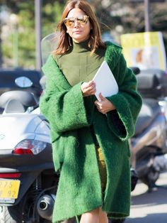 An olive green turtleneck is paired with a miniskirt, green wool coat, and mirrored sunglasses