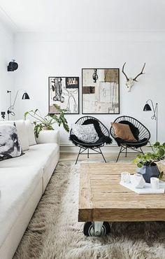 salon design scandinave, chaises en fer noir, table basse bois brut, tapis en fourrure beige, canapé chic couleur champagne