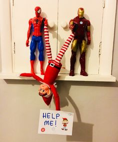 Elf on the Shelf being dangled by Spider-Man and Iron Man.