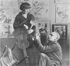 """""""Músicos callejeros"""", 1920. Aquí, la pareja aparece retratada con los dibujos no objetivos de Rodchenko de fondo. Aunque la fotografía se hizo según el estilo de ella, pues sus poses recuerdan a sus figuras, Stepanova parece pasiva y dependiente en la fotografía. #ProgramaNosotras"""