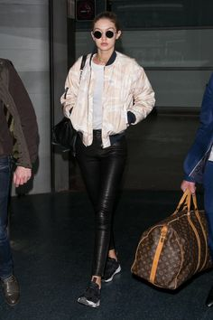 November 27, 2016  In tight leather leggings and a Ganni pastel bomber jacket at Aeroport Roissy in Paris, France.